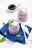 Blueberry yogurt. Fresh homemade blueberry yogurt in glass jars stock photo