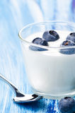 Blueberry yogurt in a glass  on blue Royalty Free Stock Image