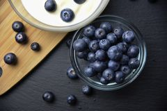 Blueberry yogurt in glass bowl on wooden table Stock Photos