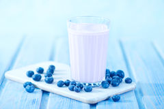Blueberry yogurt. In glass and on a table royalty free stock photo