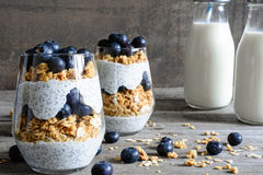 Blueberry yogurt parfait with granola and chia seeds and bottles of milk. For healthy breakfast on rustic wooden table stock images