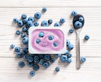 Blueberry yogurt in plastic jar on wooden table. Fresh yogurt. Healthy food concept. High resolution product. Top view royalty free stock images