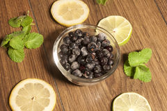 Blueberrys in a glas bowl. Between lemon, mint and lime, on wooden background Stock Photography