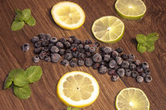 Blueberrys, between mint, lemon and lime. On wooden background Royalty Free Stock Photo