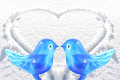 Bluebird lovebird glass art with heart snow background Stock Photo