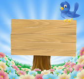 Bluebird sitting on wood sign with flowers Stock Photo