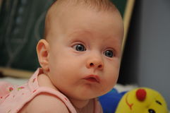 Blueeyed baby looks interested Stock Images