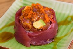 Bluefin tuna sashimi with caviar and avocado served on a square plate with soy sauce. Close up royalty free stock photo
