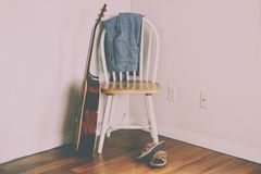 BlueJeans Hanging On Empty Chair. BlueJeans hanging on back of empty chair with sandals on floor and acoustic guitar royalty free stock photography