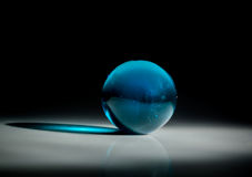 Bluel glass ball. Blue glass ball on dark background stock images