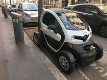 Bluely electric car sharing Renault Twizy plugged in the street royalty free stock photos