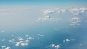 bluen clouds skywhite Sikt av moln och land från ett flygplanfönster arkivfilmer