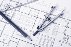 Blueprint background. Pencil and divider on top of a floor plan. Tinted photo stock image