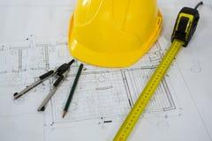 Blueprint con la misura di nastro, la matita, le bussole della vite con testa zigrinata ed il casco Fotografia Stock Libera da Diritti