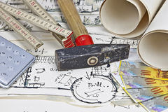 The blueprint of a house. With two paper rolls, a calculator, a hammer, money and a rule Royalty Free Stock Photography