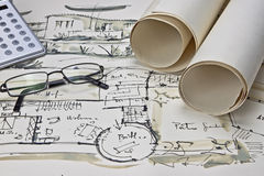 The blueprint of a house. With two paper rolls, eyeglasses and a calculator Royalty Free Stock Images