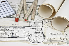 The blueprint of a house. With two paper rolls, a calculator and a rule Stock Photos