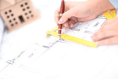 Blueprint of office building over blurred adult male engineer examining documents. In office Stock Photography