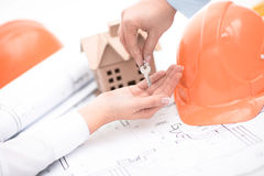 Blueprint of office building over blurred adult male engineer examining documents. In office Stock Photos