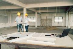 Blueprint, ordinateur portable, et outils industriels au chantier de construction avec deux ingénieurs ou architectes travaillant Image stock