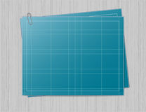 Blueprint paper on grey background. Blank blueprint paper with one sheet of the same paper underneat and joined with the paperclip. Both blueprints are layed on Stock Photos
