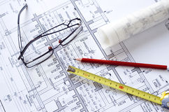 Blueprint pencil tape measure. Glasses, red pencil, yellow tape measure lying on a blueprint Royalty Free Stock Photography