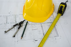 Blueprint with tape measure, pencil , thumbscrew compasses and hard hat Royalty Free Stock Photo
