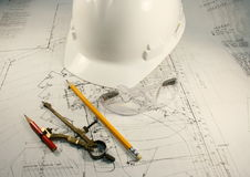 Blueprint work. White hardhat with compus pencil and glasses over blueprints Stock Images