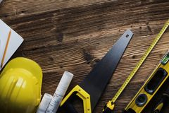 Construction and renovation concept. Place for typography or text. Blueprints and building contractor tools on wooden table. Top view stock images