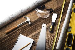Construction and renovation concept. Place for typography or text. Blueprints and building contractor tools on wooden table. Top view stock photography