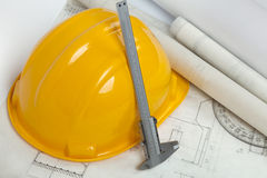 Blueprints and construction tools on table. Hard hat, blueprints and micrometer on table Stock Photo