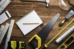 Contractor concept background. Place for typography. Blueprints and contractor tools and equipment on wooden table. Top view stock images