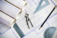 Drafting. Blueprints on a drafting table with a compass and rulers stock photo