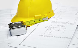 Blueprints with hardhat and tape measure Royalty Free Stock Images