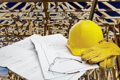 Blueprints with hardhat, workgloves, reading glasses and framed wood structure in background Stock Photography