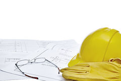 Blueprints with hardhat, workgloves and reading glasses Royalty Free Stock Photo