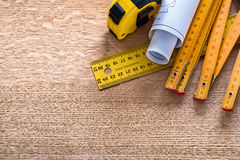 Blueprints and instruments of measurement on oaken. Wooden board construction concept Royalty Free Stock Image