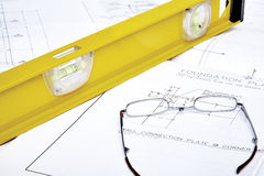 Blueprints with reading glasses and level Royalty Free Stock Images
