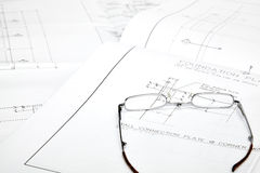Blueprints with reading glasses Stock Photos