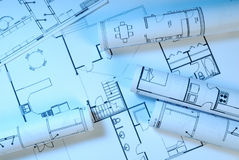 Blueprints. Rolled and lying blueprints in blue light Royalty Free Stock Photos