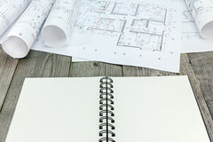 Blueprints rolls with plans and notepad on gray wooden table Stock Photography