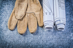 Blueprints safety gloves on metallic background construction con Stock Photos