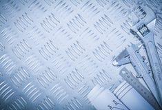 Blueprints slide caliper monkey wrench on channeled metal sheet Stock Image