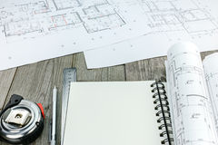 Blueprints with tape measure and notepad on wooden table Royalty Free Stock Photo
