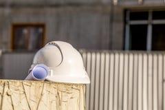 Blueprints and white helmet. Stock Photos