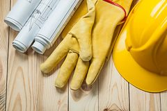 Blueprints yellow gloves and construction helmet on wood boards royalty free stock photography