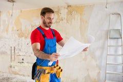 Blueprnts do watchig do trabalhador manual das renovações home fotos de stock