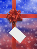 Blue and red present. Blue and red paper with stars and red ribbon includes a white card to write on it Royalty Free Stock Image