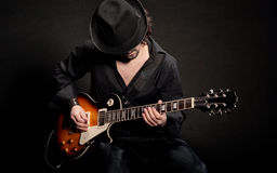 Blues. A man playing eletctric guitar in black clothes Stock Photography