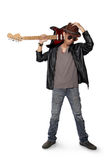 Blues guitarist pose. Young blues rocker dude standing, holding his hat while carrying guitar on his shoulder, isolated on white background Royalty Free Stock Photo
